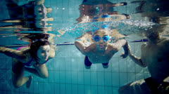 Happy and attractive mixed race family swimming underwater smiling at the camera - stock footage