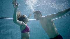 Attractive and playful couple underwater kissing and embracing Stock Footage
