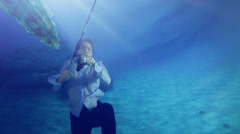 Mysterious underwater woman with a fishing rod in deep blue water Stock Footage
