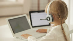 Beautiful little girl in headset sitting at table working on laptop turning Stock Footage