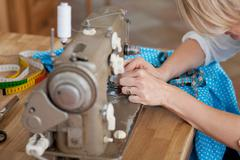 sewing by machine - stock photo