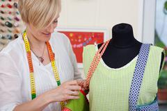 designer fixing bag's strap on mannequin - stock photo
