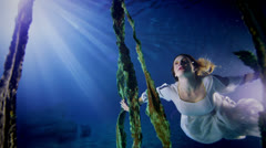 Beautiful mysterious underwater woman in white dress Stock Footage