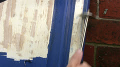 Close up of blue paint being removed from a kitchen cupboard door - stock footage