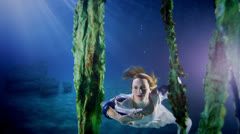 Beautiful mysterious underwater woman in white dress - stock footage