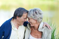 Sweet elderly couple in love sitting near the lake Stock Photos