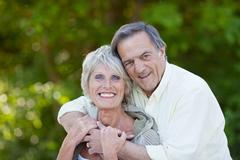 happy senior couple hugging and smiling - stock photo