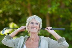 senior woman holding golf club while looking away - stock photo