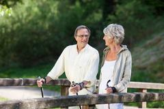 senior couple doing a nordic walk on bridge - stock photo