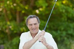 senior man playing golf in park - stock photo