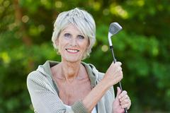 old lady holding the golf stick - stock photo