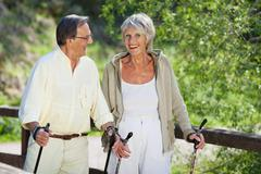 senior woman trekking with husband in forest - stock photo