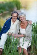 loving senior couple sitting by lakeside in park - stock photo