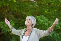 Senior woman with arms outstretched in park Stock Photos