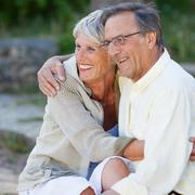 senior couple looking away while embracing in park - stock photo