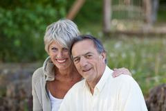 happy senior couple smiling in park - stock photo