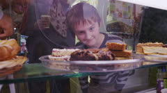 Cute little boy choosing from a selection of fresh pastries in a cafe or bakery - stock footage