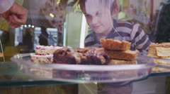 Stock Video Footage of Cute little boy choosing from a selection of fresh pastries in a cafe or bakery