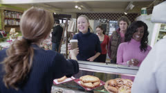 Happy customers buying coffee and fresh pastries in a cafe - stock footage