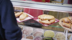 Happy female customer choosing from a selection of fresh pastries in a cafe - stock footage