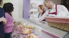 Happy customers buying coffee and a fresh pastries in a cafe or bakery - stock footage