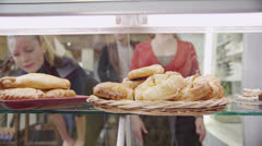 Happy customers looking through a glass cabinet and choosing fresh pastries - stock footage