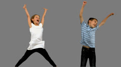 Brother and sister jumping together on grey screen Stock Footage