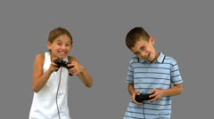 Siblings playing video games on grey screen Stock Footage