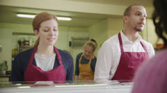 Friendly staff serving customers with a smile at the bakery counter - stock footage