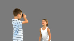Brother taking pictures of his sister jumping on grey screen Stock Footage
