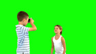 Brother taking pictures of his sister jumping on green screen Stock Footage