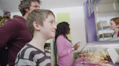 Cute and happy little boy choosing a fresh savory pastry at the bakery counter Stock Footage