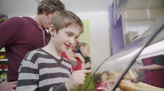 Cute and happy little boy choosing a fresh savory pastry at the bakery counter - stock footage