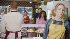 Happy customers being served by friendly staff at the bakery counter - stock footage