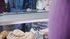 Cute little boy choosing a fresh pastry at the bakery counter - stock footage