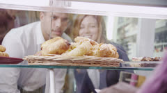 Happy attractive young couple choosing fresh pastries at the bakery counter - stock footage