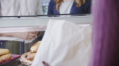 Happy attractive young couple buying fresh pastries at the bakery counter - stock footage