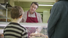 Friendly male shopkeeper serving customers with fresh pastries - stock footage