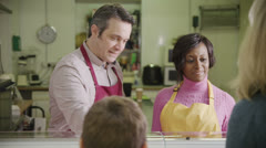 Friendly male and female shopkeepers serving customers with coffee and pastries - stock footage