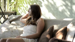 Beautiful girl resting on garden swing - stock footage