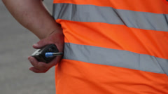 Clumsy security with walky-talky in orange uniform standing Stock Footage
