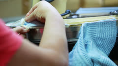 Operator straightens loop on knitted clothes Stock Footage