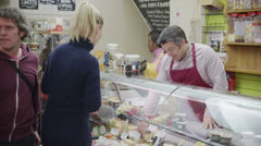 Friendly delicatessen staff serving customers with a smile at the cheese counter - stock footage