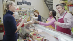 Friendly delicatessen staff serving customers with a smile at the cheese counter Stock Footage