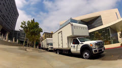 POV Cycling Past Movie Equipment Trucks On Location In Downtown L.A. Stock Footage