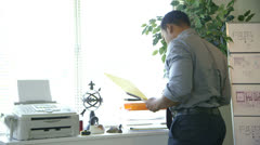 Businessman walks to his desk and works Stock Footage