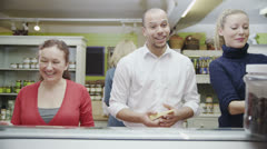 Happy customers being served by friendly staff at the delicatessen - stock footage