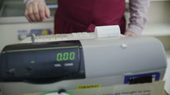 Shopkeeper behind the counter takes a credit card payment from a customer - stock footage