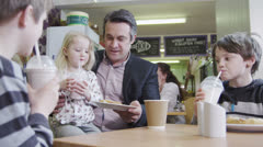 Happy affectionate family enjoying snacks and drinks in a cafe Stock Footage
