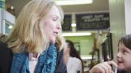 Cute little boy in a cafe enjoys sharing his milkshake Stock Footage